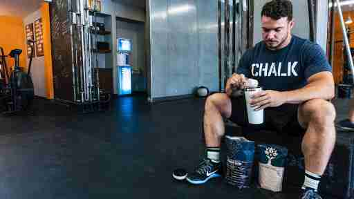 man drinking a protein shake in the gym after a workout