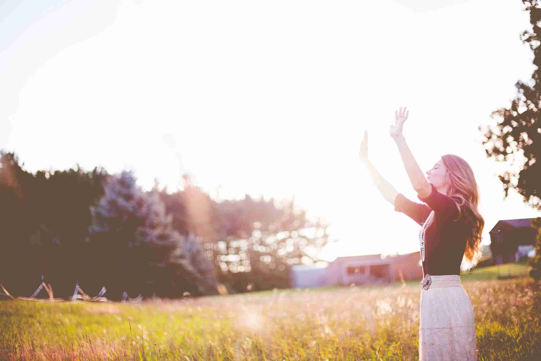 Woman Holding Hands Up in a Field