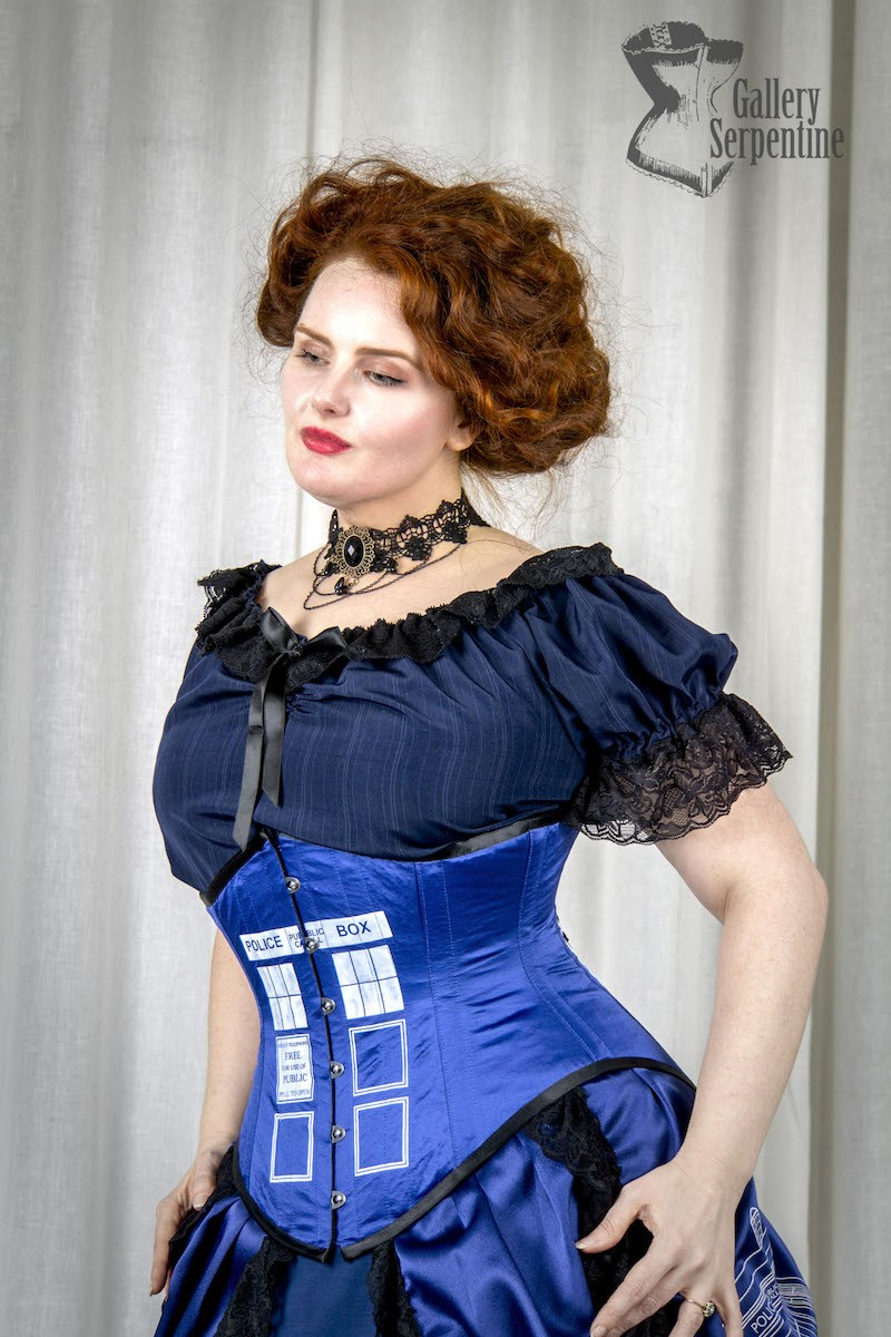 blue under bust Tight laced Tardis police box screen print corset made in Australia worn by a red haired pre-raphelite looking model