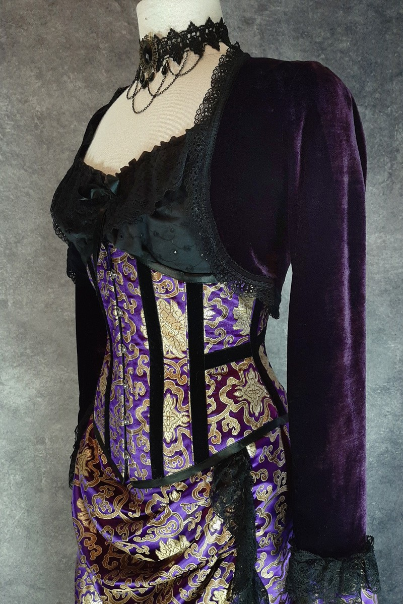 side front view of the royal purple gold brocade under bust corset worn with an amethyst velvet bolero