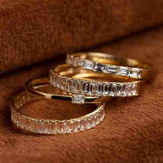 A collection of four gold rings with baguette diamonds