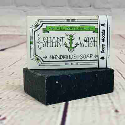 Picture of a box of Shart Wash Natural Handmade Bar Soap Deep Woods scent sitting on a black bar of soap with a wood background