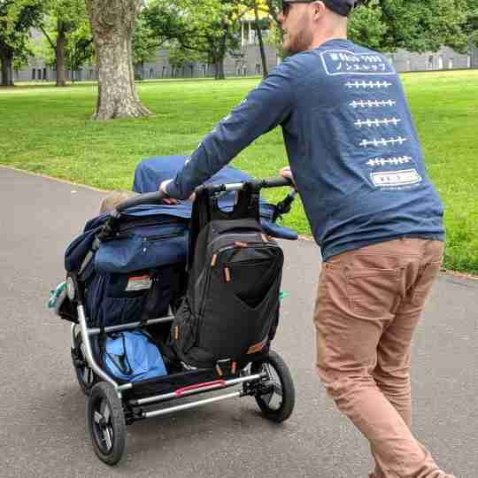 father pushing pram with backpack attached
