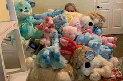 Surrounded by a mountain of stuffed animals.