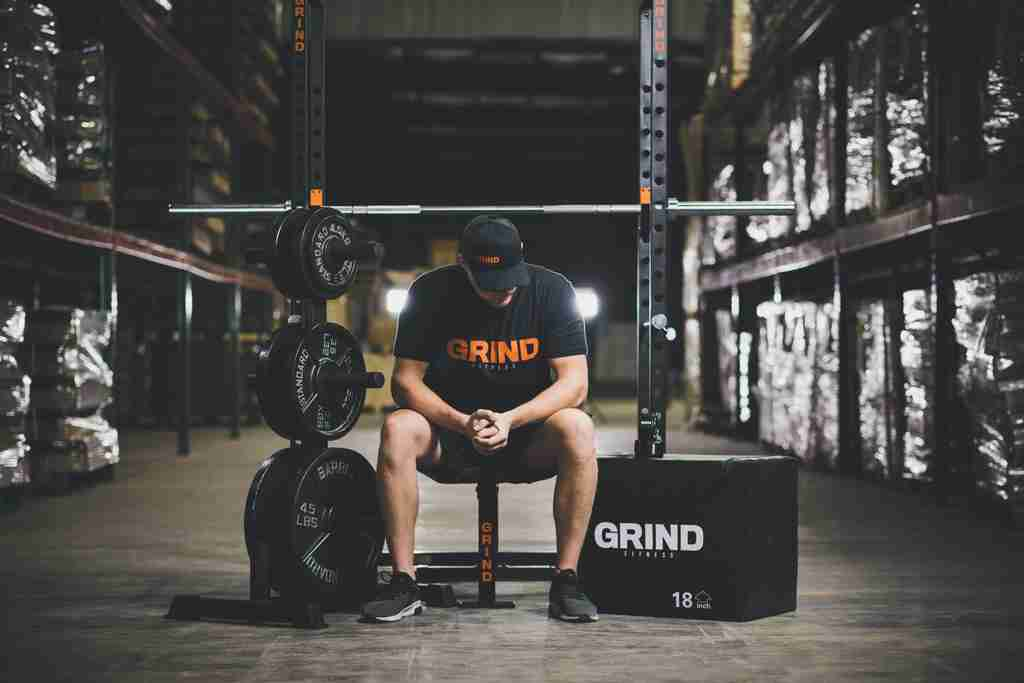 GRIND Equipment plus man with hat looking down. Sitting on bench.