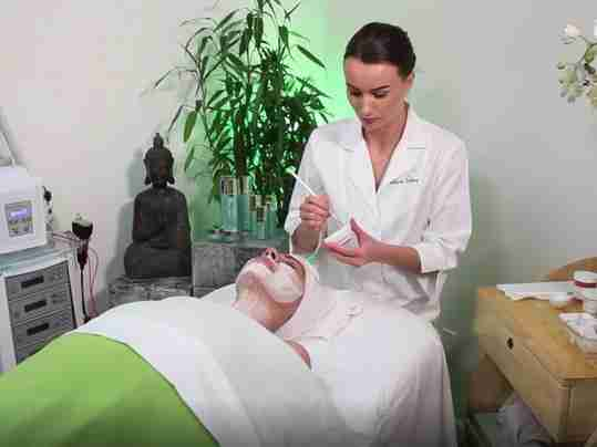 Christine Valmy expert esthetician applying a professional specialty care facial mask during a spa facial treatment