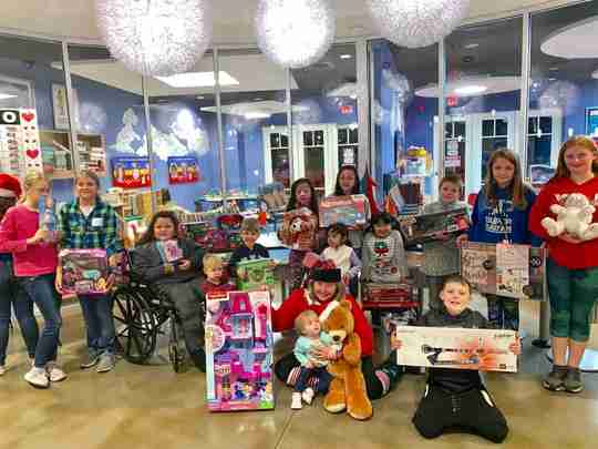 A group of kids at a hospital with presents.