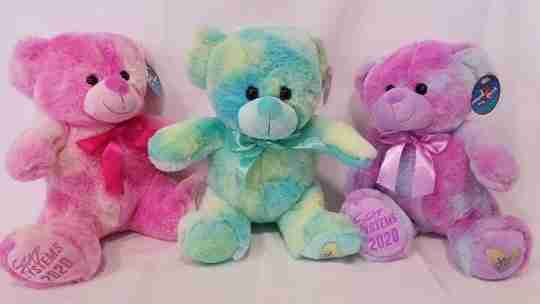 Three tie-dye bears with writing on its foot
