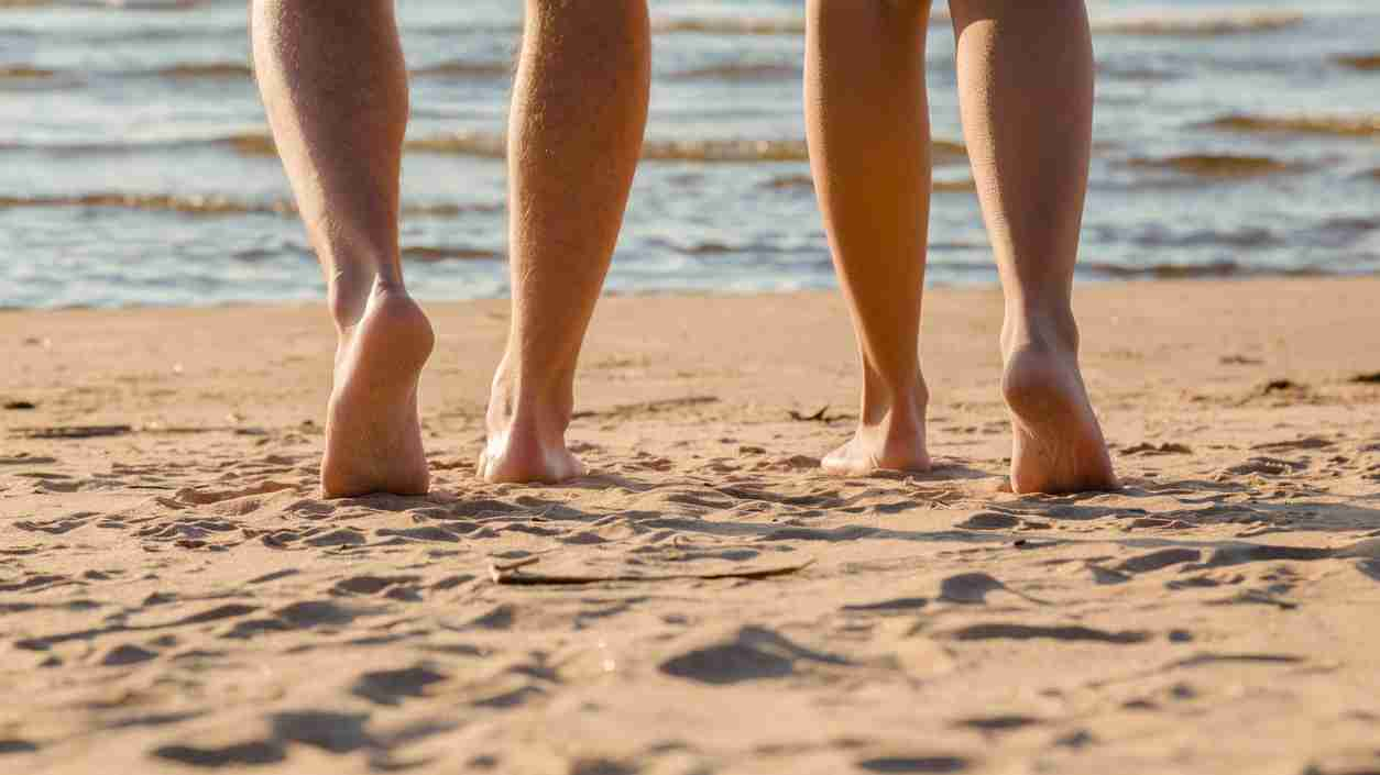 Young couple's barefoot going to swim in cold sunny day. Woman legs have goosebumps. Back view. Closeup