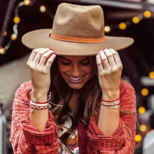 A woman wearing a hat and bracelets