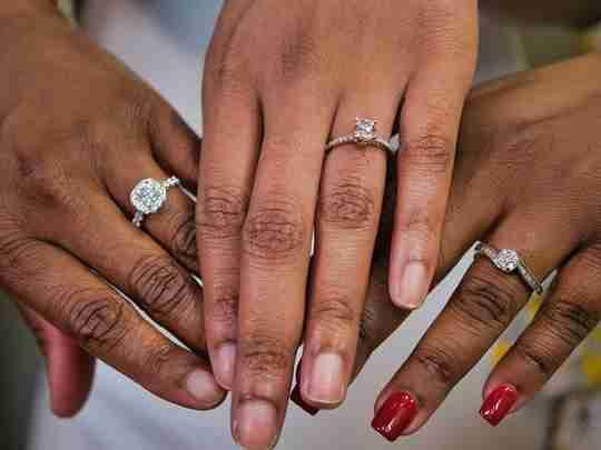 Three hands wearing diamond rings