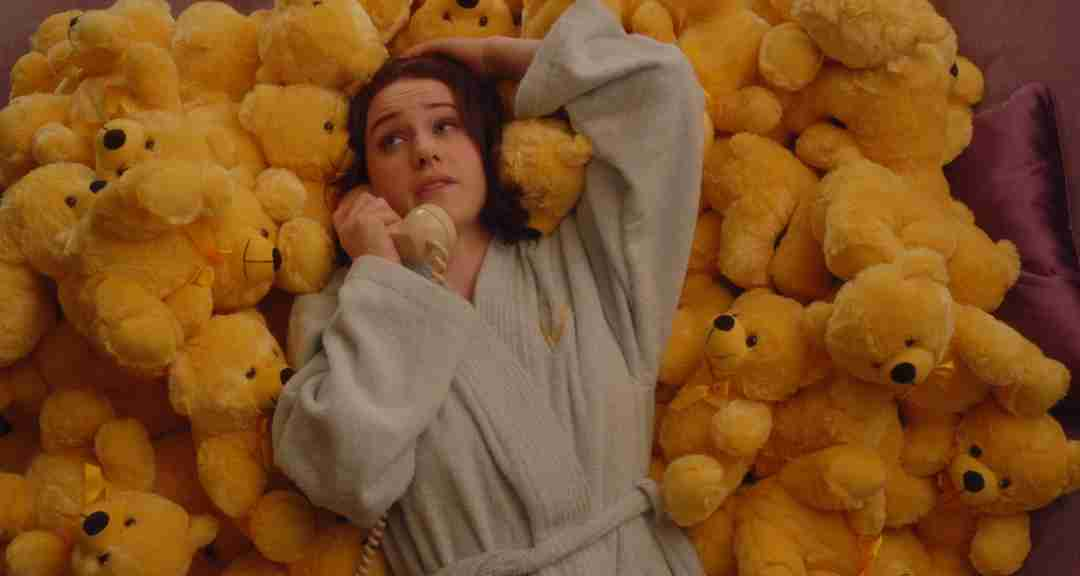 Mrs. Maisel, resting on top of a pile of yellow Colorama Bears, while wearing a robe and talking on the phone.