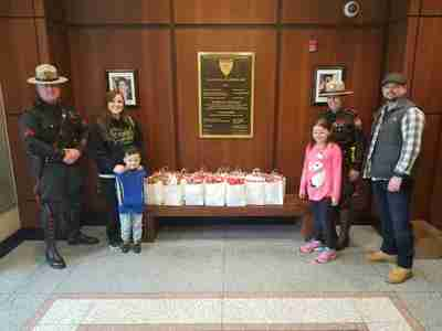 Two officers, a man , a woman, and two kids standing in between a a bunch of gift bags on a table