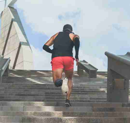 A man running up stairs after taking his carnitine supplement.