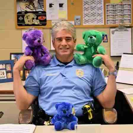 Police officer with several bears.