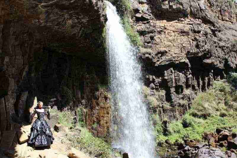 Silvia in full Gothic Baroque Scrolls Gown standing underneath a cascading waterfall near Junee, NSW, Australia