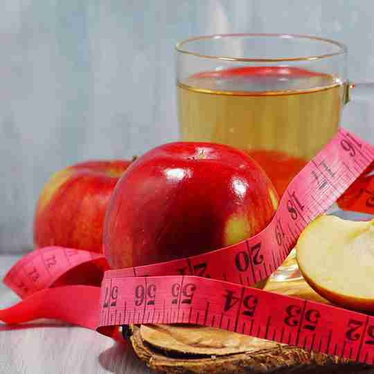 Cup of apple cider vinegar with red apples and a red measuring tape