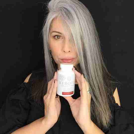 Model With Long Gray Hair Holding a Bottle of Kerotin Hair Vitamins