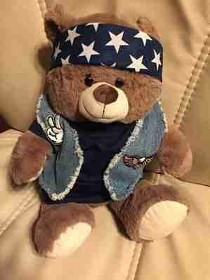 A brown bear wearing a black shirt and a jean vest with a american flagged bandanna