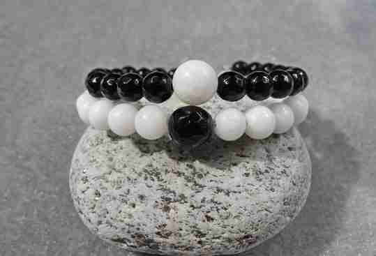 Two black and white onyx bracelets on a stone