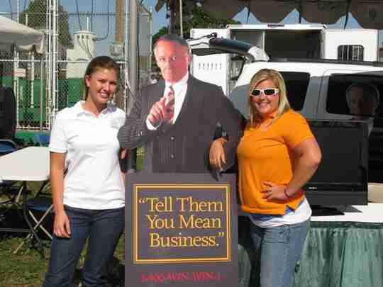 Two women standing next to a standing poster guy