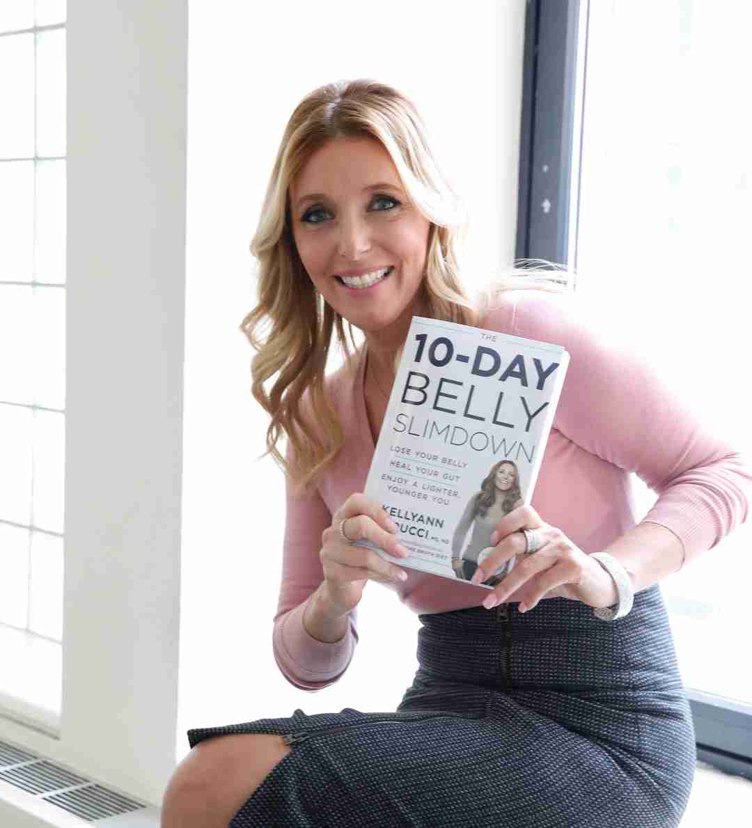 Dr. Kellyann Petrucci holding the 10-Day Belly Slimdown book