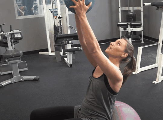 Fit Lady Exercising in Gym on Fitness Ball