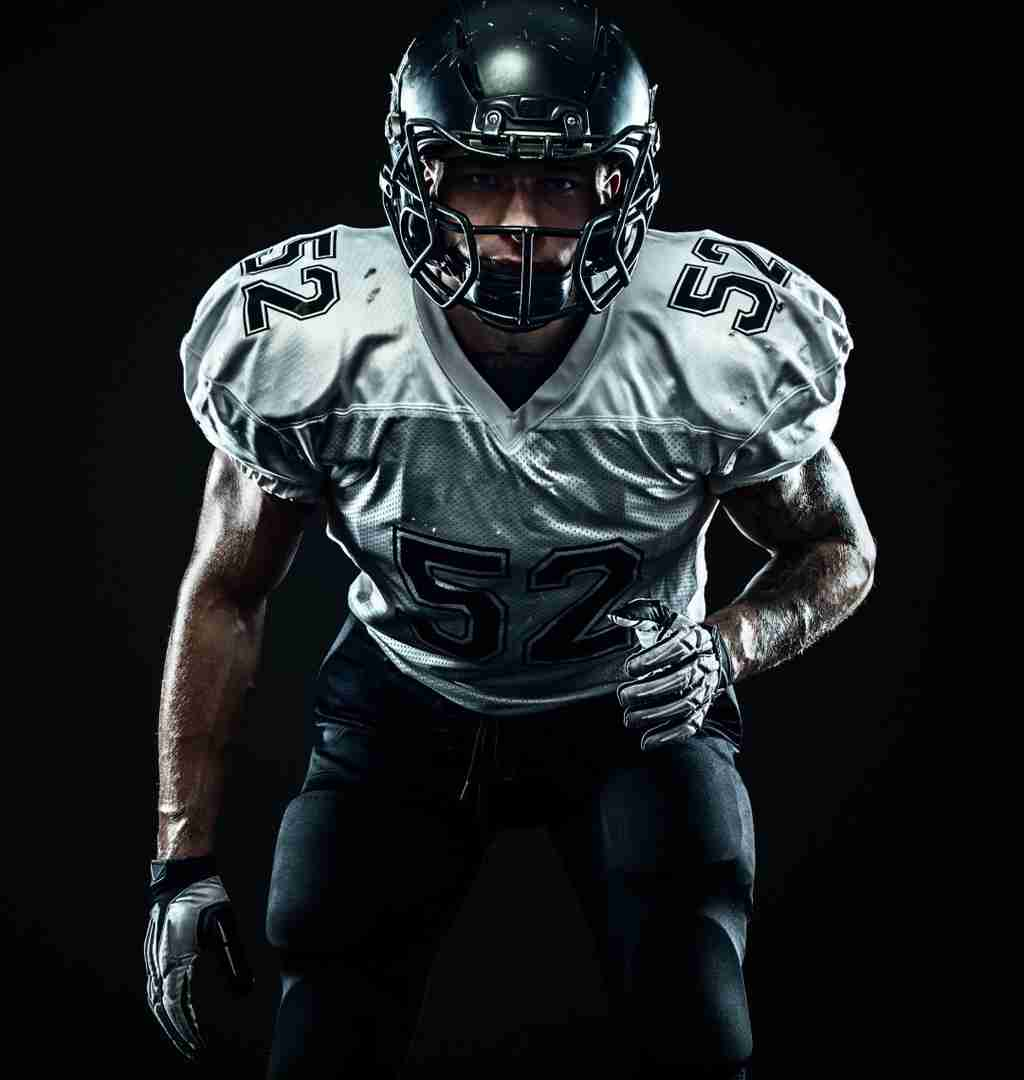 A football linebacker ready to make a tackle with explosive strength power.
