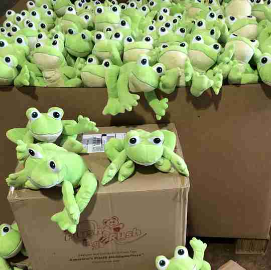 A big pile of green frogs on boxes.