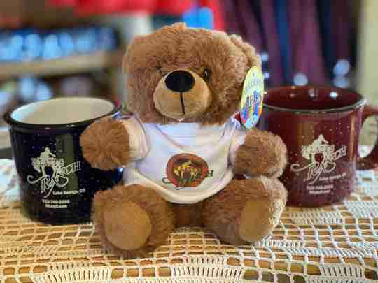 A brown bear with a white shirt next to 2 mugs