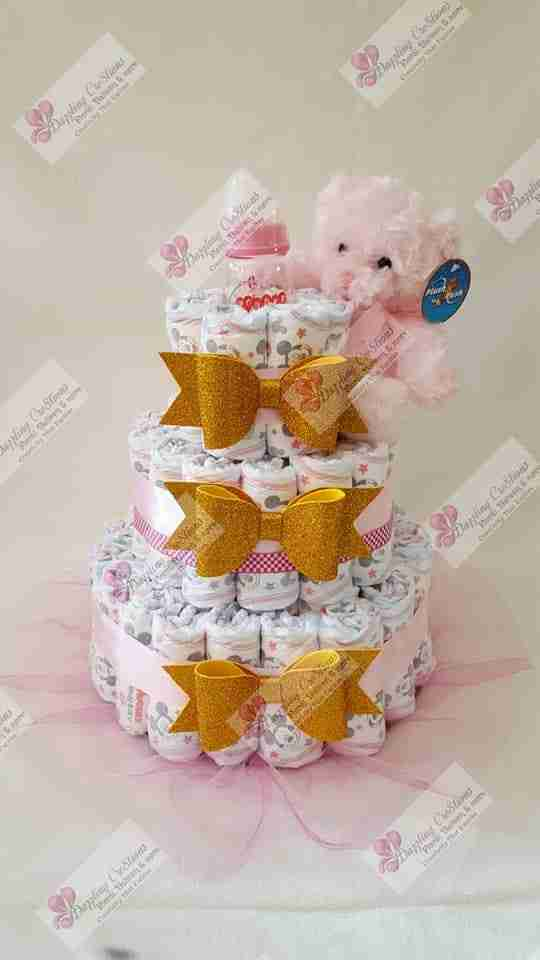 A pink bear sitting on top of a decorated wrapped clothes that look like a cake