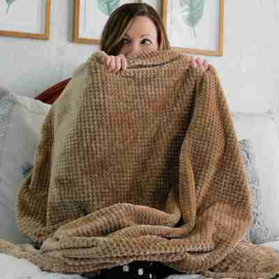 picture of a woman sitting on a bed with a tan throw blanket covering her mouth