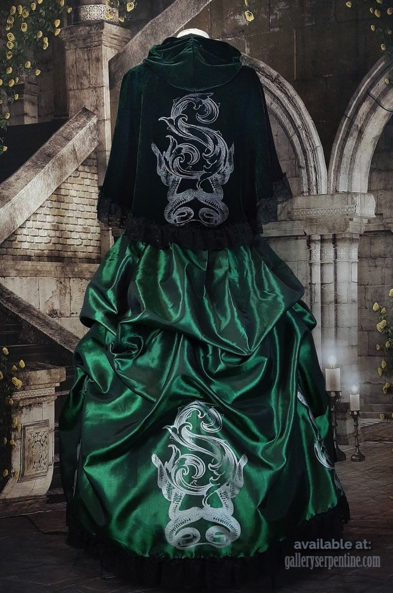 BACK VIEW OF THE NEW DELUXE SLYTHERING CAPE IN DARK GREEN VELVET WORN OVER A MATCHING EMERALD TAFFETA VICTORIAN SKIRT