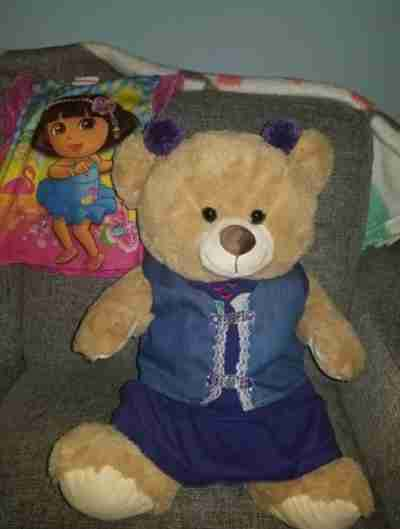 A beige bear wearing a purple dress and purple hair balls on top of its head sitting on a couch
