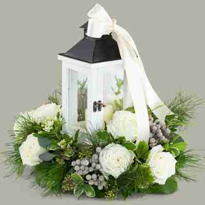A white wooden lantern surrounded by white roses
