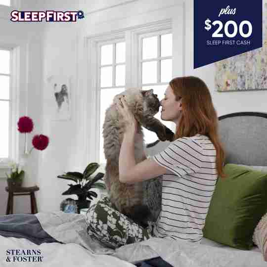 Woman snuggles her cat on a Stearns & Foster mattress