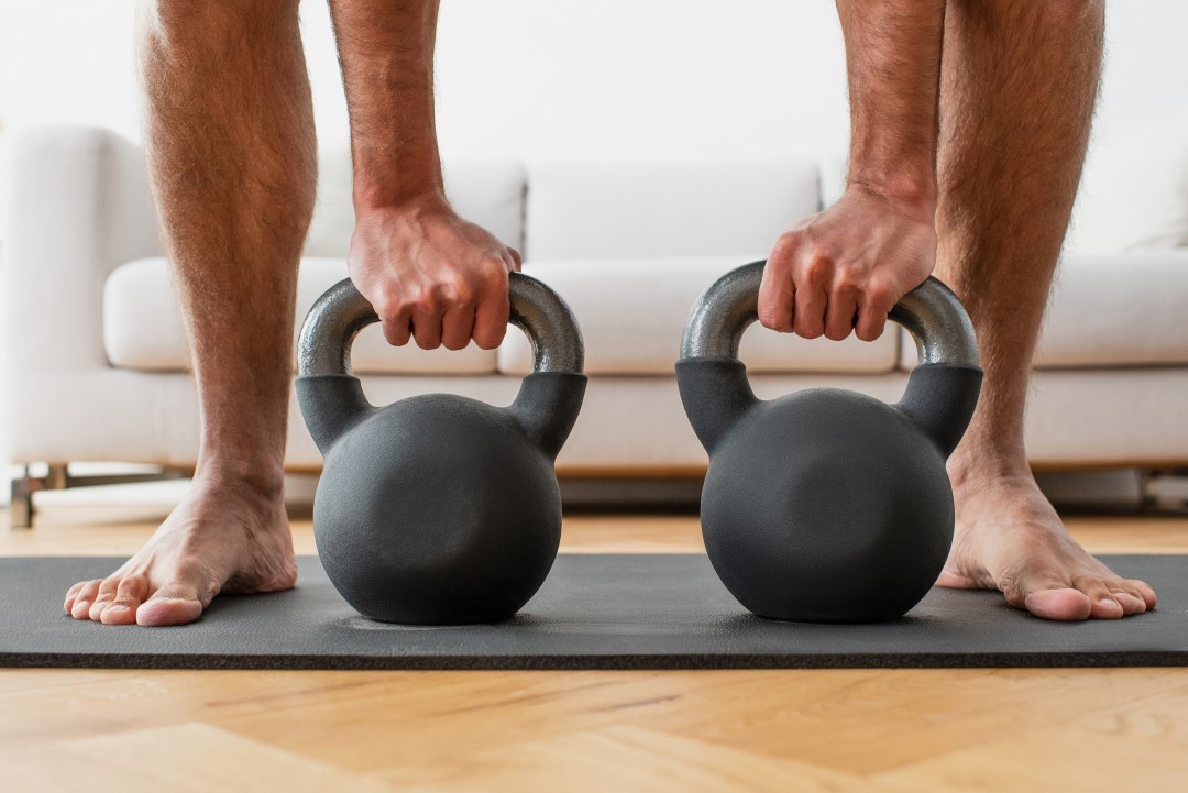 A male athlete workout barefoot with two kettlebells.