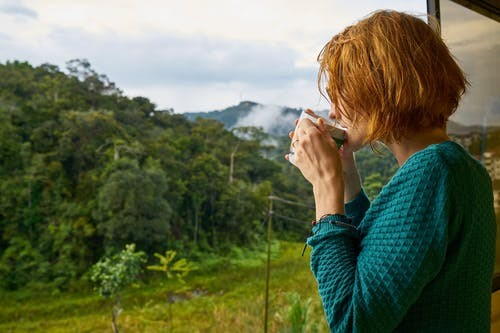 A woman sipping on a cup of hot beverage enjoying a beautiful view of the mountains.