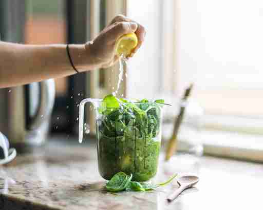 spinach in a blender with greens lemon juice