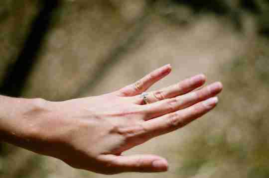 Woman's hand with a silver ring on the ring finger