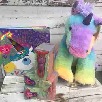 A rainbow unicorn next to bars of soap and a book