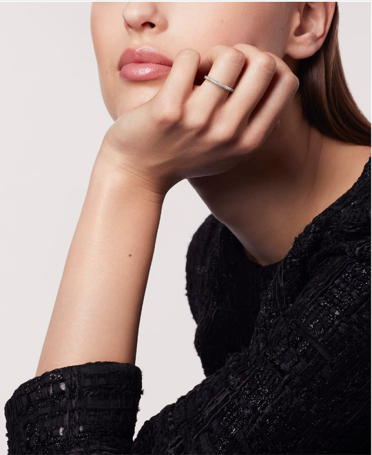 A woman wearing a thin Chanel ring