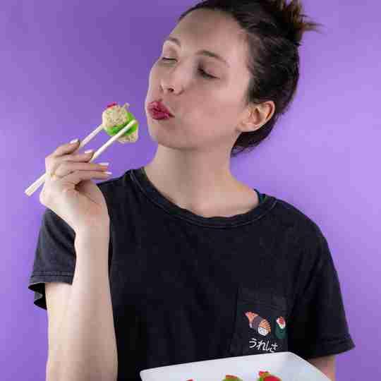 Meet Sheri - holding sushi with chopsticks