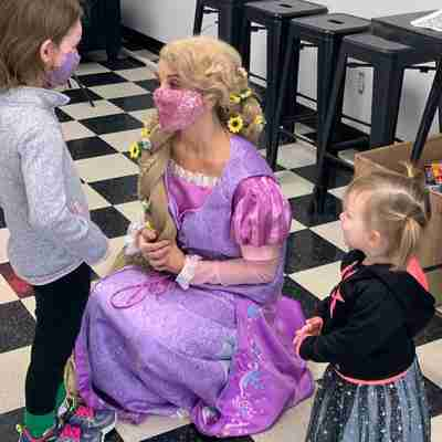 A woman dressed up like Rapunzel talking to two little girls
